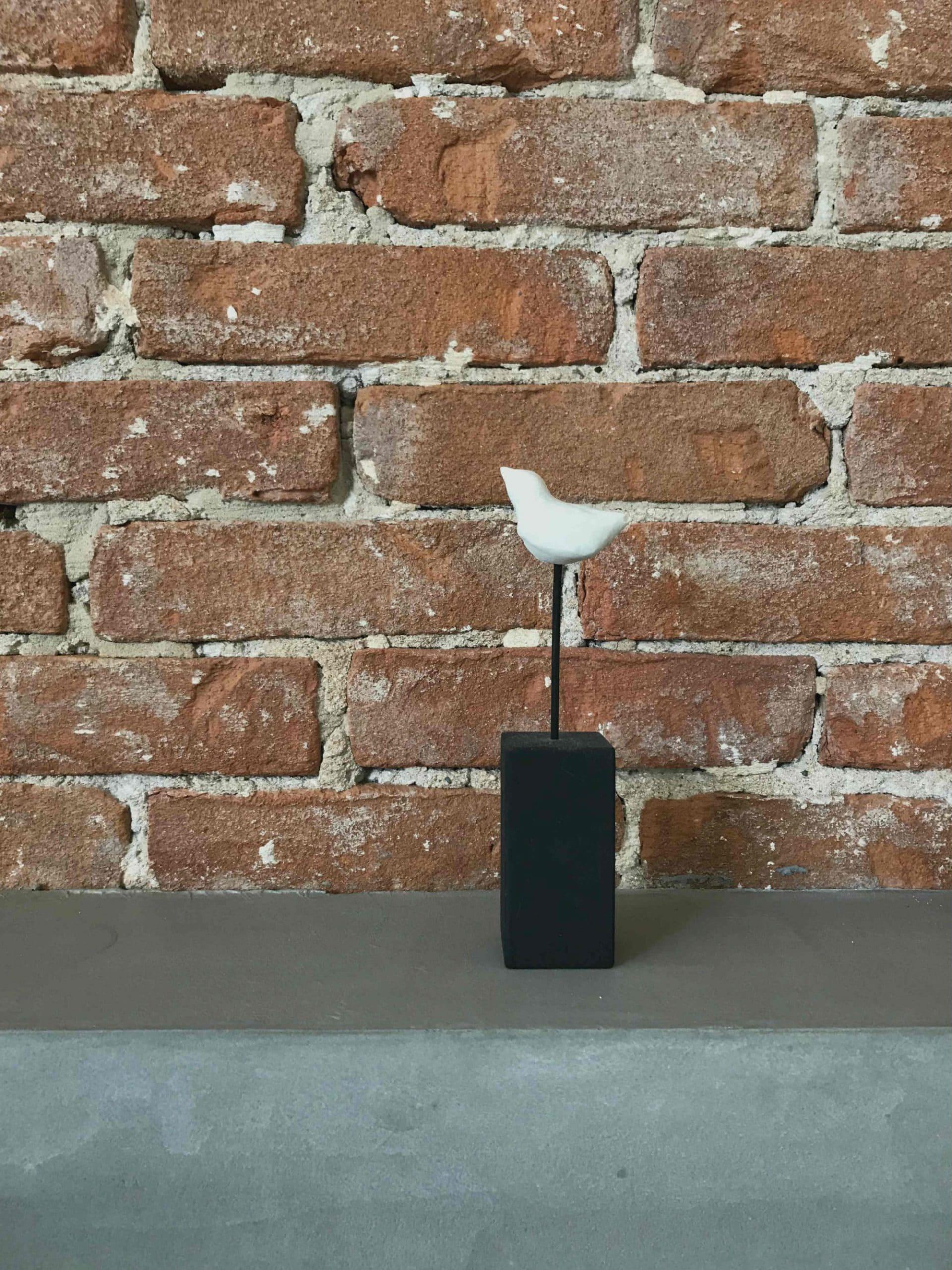 Vogel van klei op een zwarte sokkel