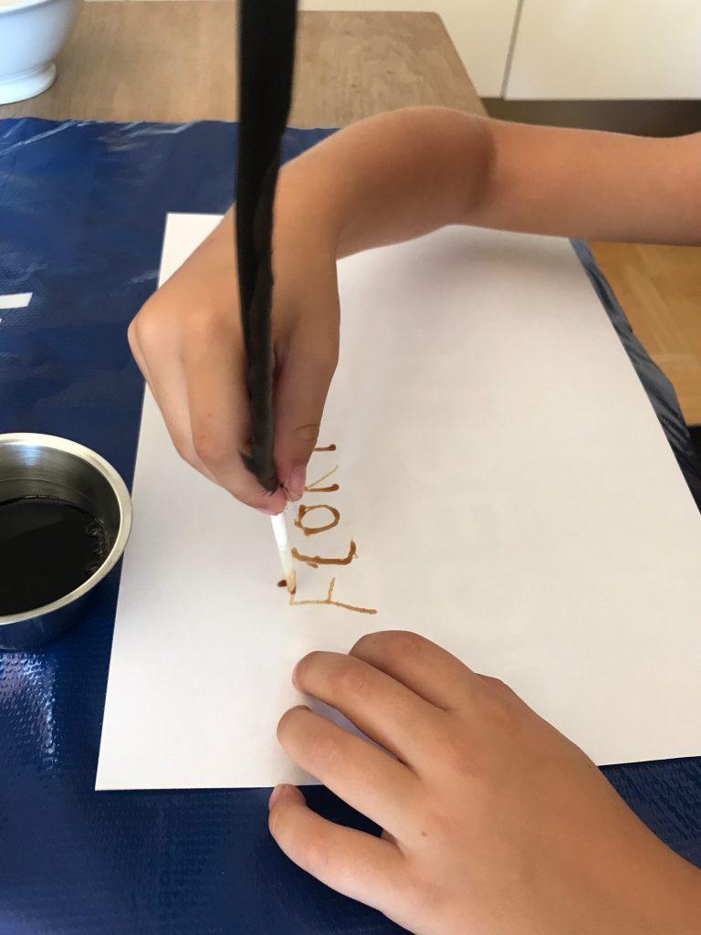 Kind maakt tekening met ganzenveer